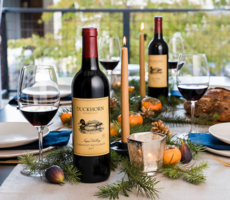 Duckhorn Vineyards wines on a holiday table with bread and candles