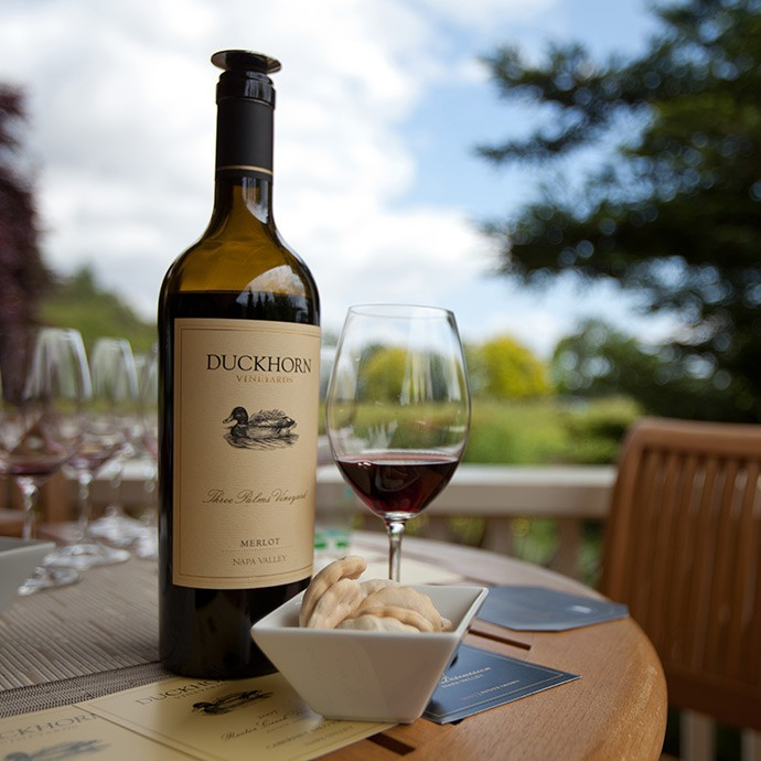 Bottle of wine and glass on the outdoor veranda at Duckhorn Vineyards