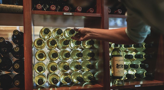 Pulling a bottle of Duckhorn wine from a storage rack