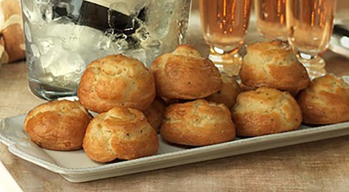 Platter of freshly baked gougeres on decorated holiday table