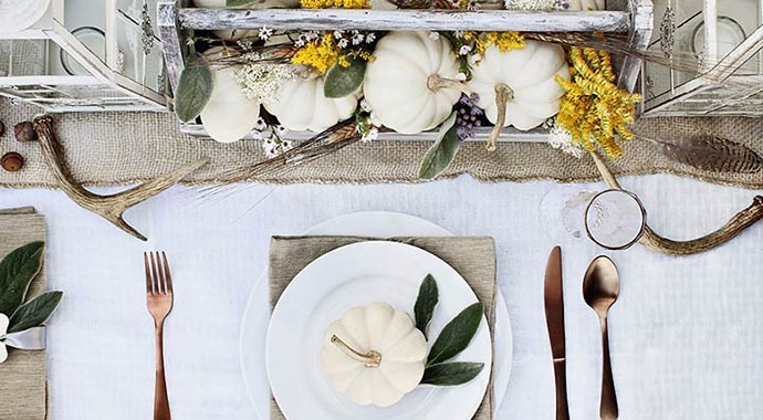 Thanksgiving table setting with fall decor and pumpkins
